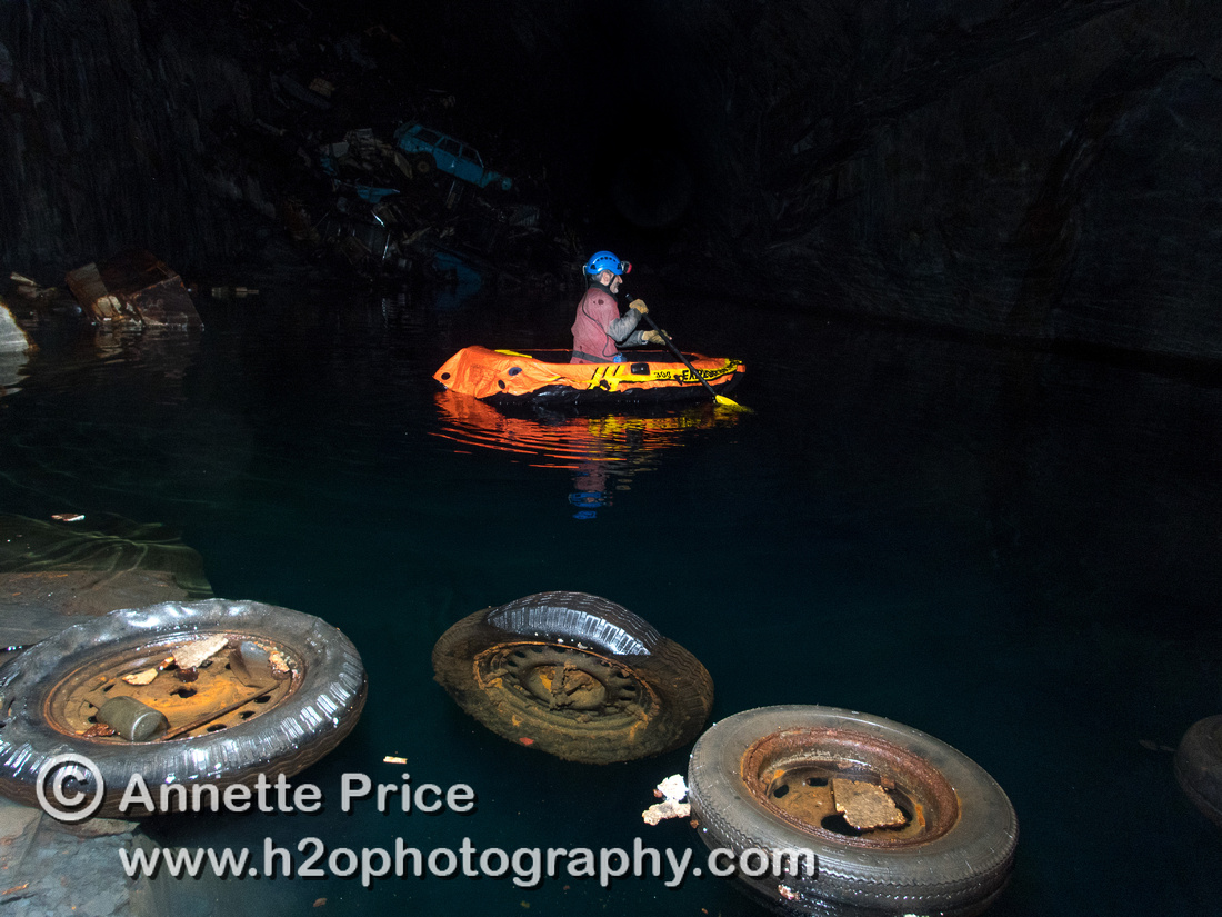 Peter Hamilton paddles past floating wheels towards the car graveyard. Gaewern Slate Mine.