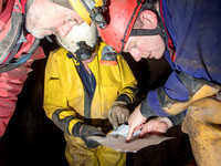 Cavers consulting a cave survey map in Slaughter Stream Cave, South Wales, UK