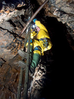 Caver Chris Crowley climbing down a ladder in Slaughter Stream Cave, South Wales, UK