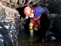 Caver Neil Montgomery in Slaughter Stream Cave, South Wales, UK