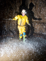 Chris Crowley walking under an underground shower.  Slaughter Stream Cave, South Wales, UK